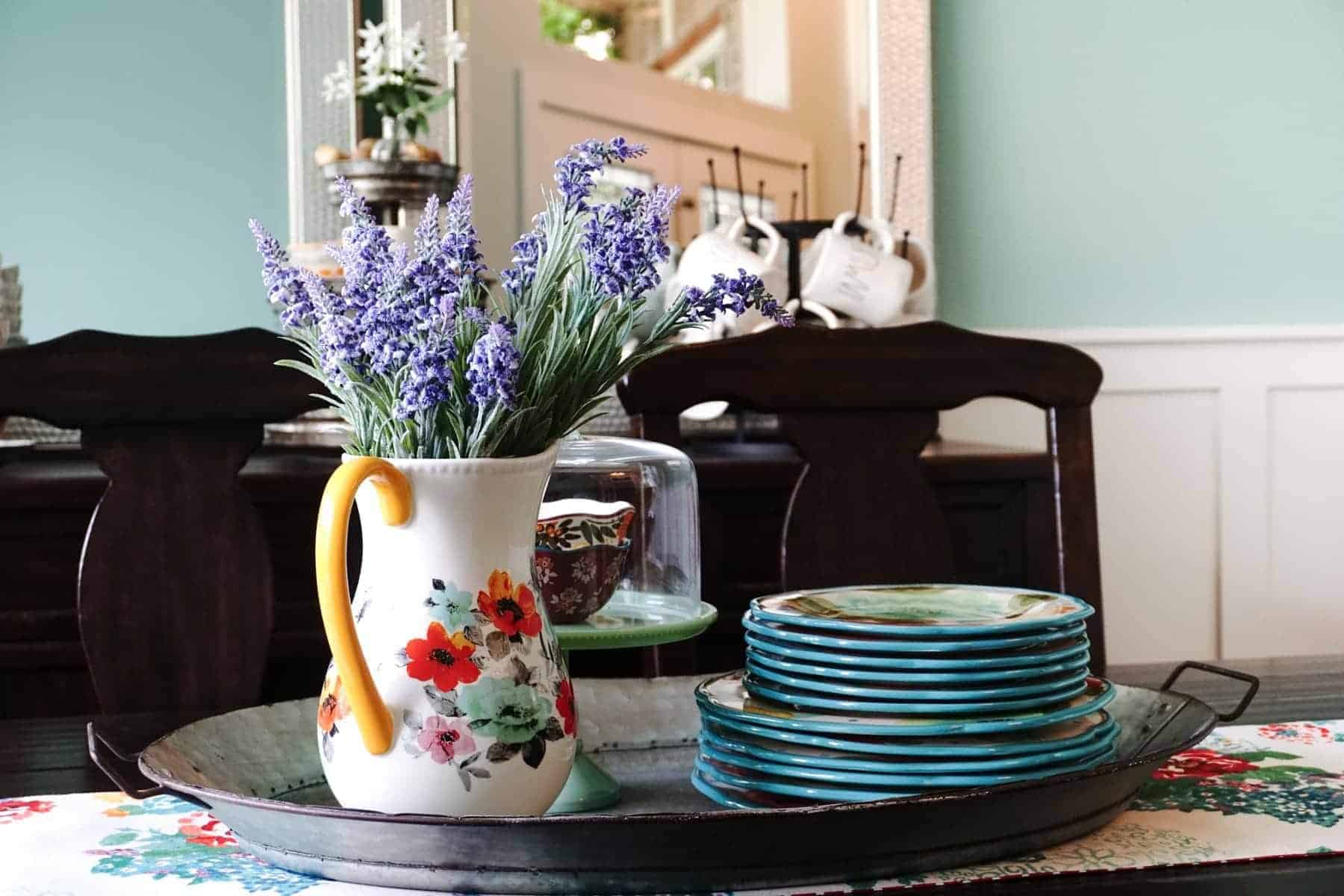 A Table Centerpiece Adorned With Lavender Flowers And Pioneer Woman Plates
