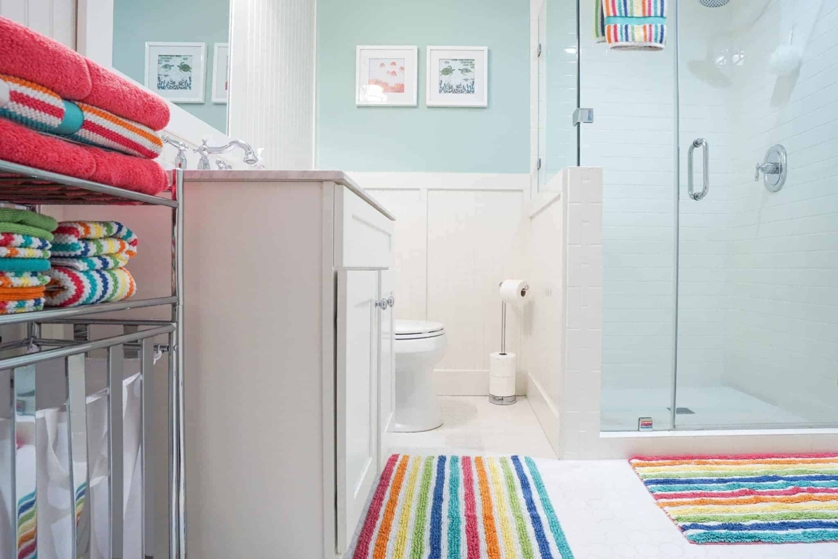 White cabinets and tile provide a canvas for endless bathroom color ideas.