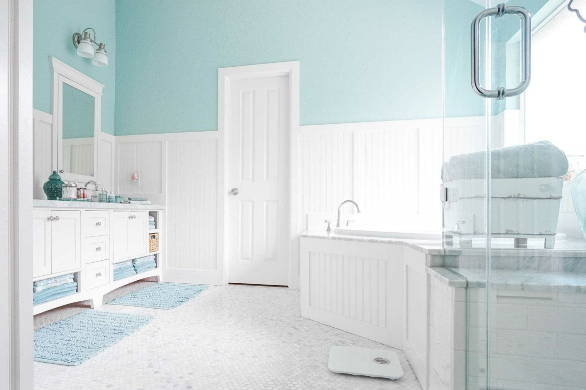 White tile and cabinets allow you to decorate your bathroom in any color scheme by swapping out bath mats and towels.