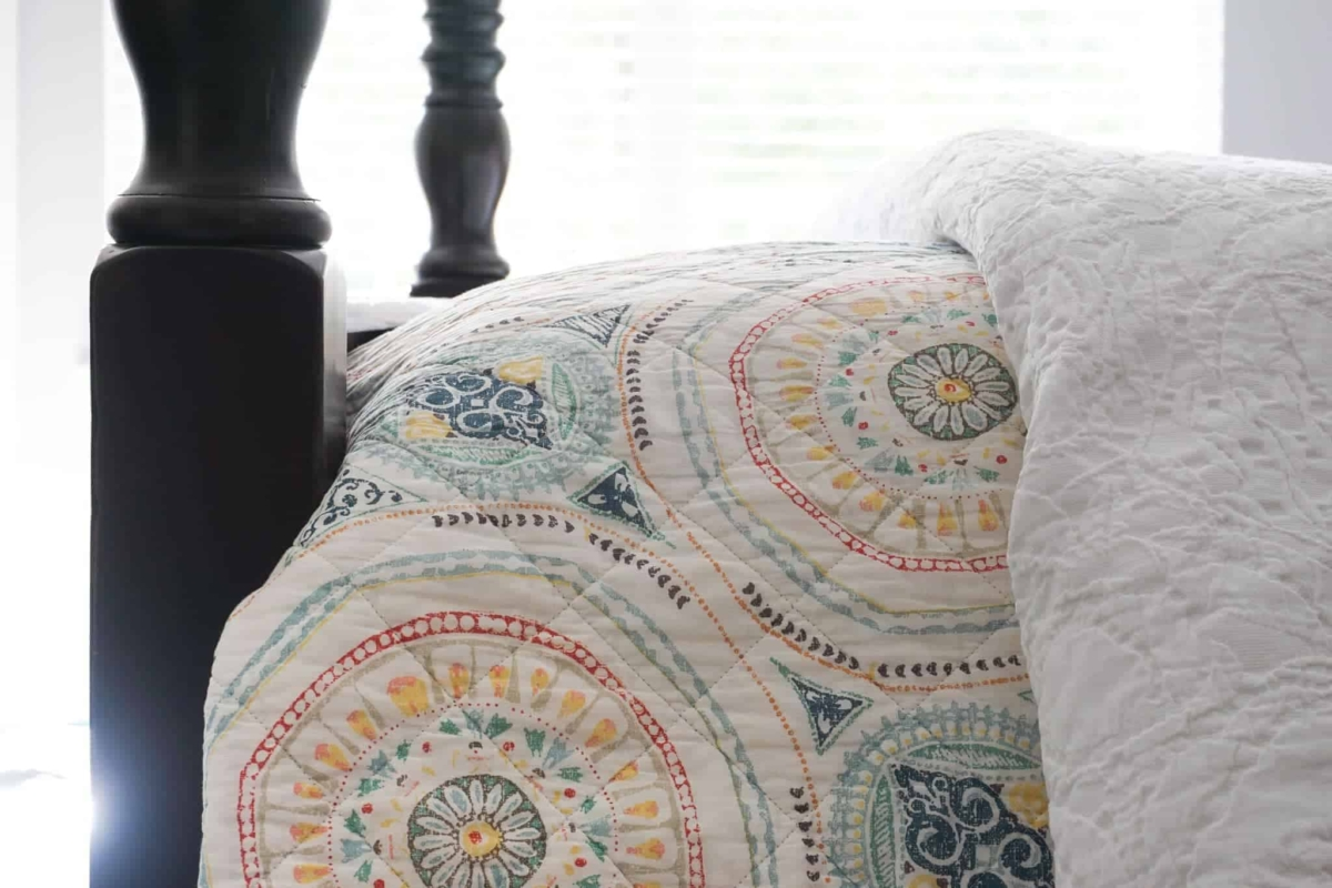 Decorate with color by using a colorful quilt layered on white bedding.