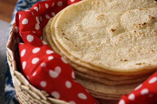 a stack of corn tortillas ready to be made into authentic mexican pork tacos
