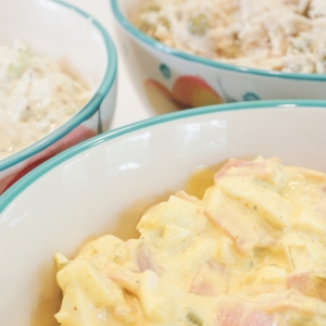 a bowl of cream cheese dip on a plate surrounded with bread crackers