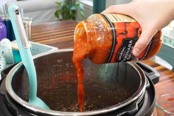 adding marinara sauce to lasagna meat sauce