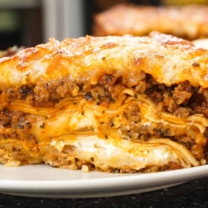 rich creamy meat lasagna on a plate with salad