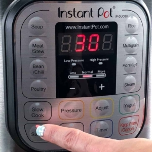 selecting the sauté function on the instant pot to make tomato soup