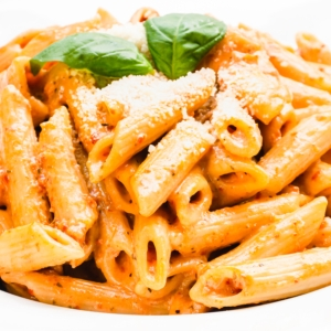 a bowl of creamy sun-dried tomato pasta topped with parmesan and basil leaves