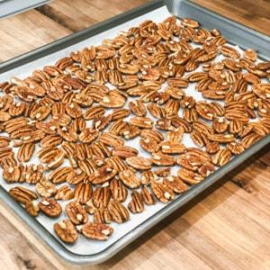 spreading pecans in a baking sheet