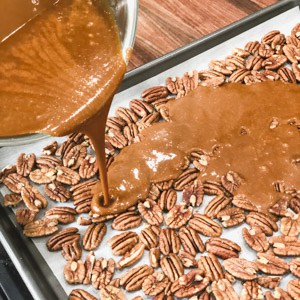 pouring toffee over pecans on a baking sheet