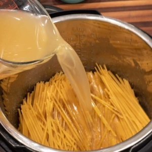 puring unsalted chicken stock over the linguine pasta in the instant pot