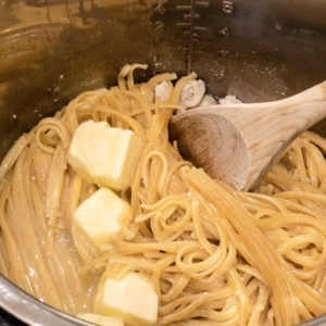 adding butter and mixing into pasta so that it will melt