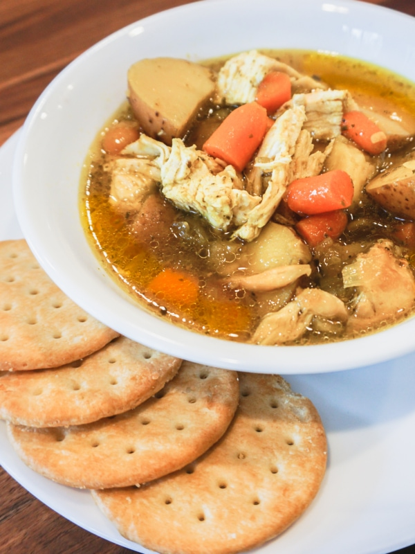 Delicious bowl of Instant Pot Chicken soup with potatoes, carrots, chicken, and crackers on the side.