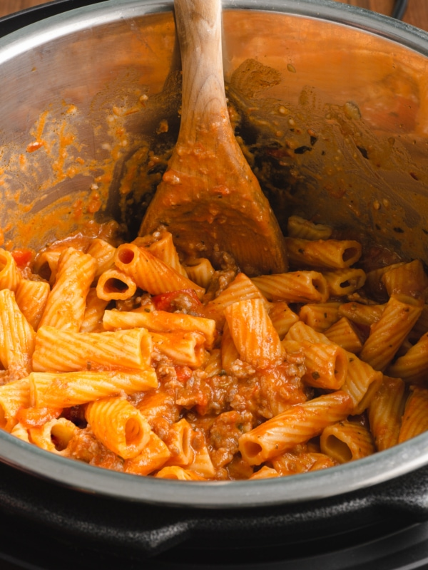 freshly made pot of instant pot creamy sausage rigatoni being mixed with a wooden spoon