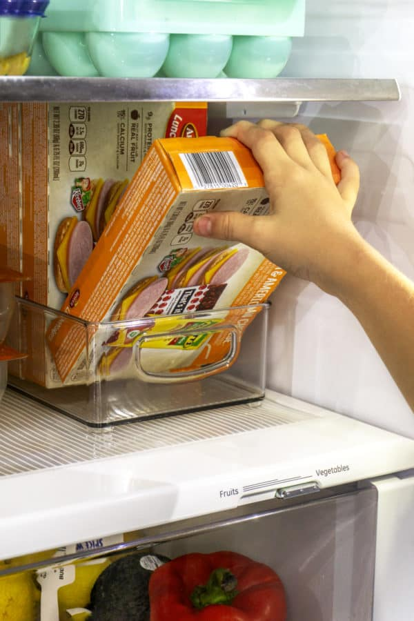 a child's hand pulling a box of armour lunchmakers plus drink from refrigerator
