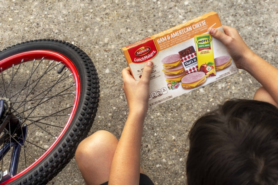 a view from above of a bike and a child holding a box of armour lunchmakers and drink ham and american cheese