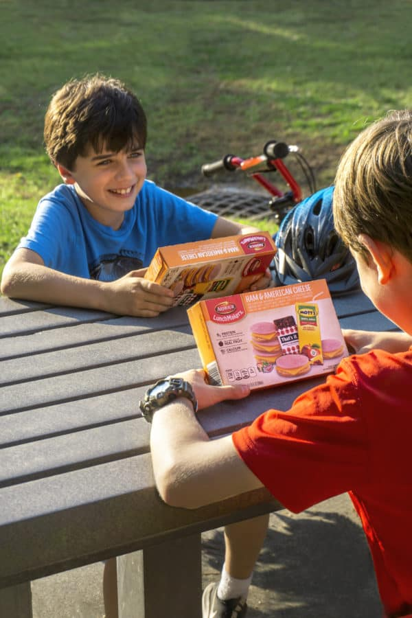 2 kids sitting on park bench each holding a box of armour lunchmakers and drink ham and american cheese