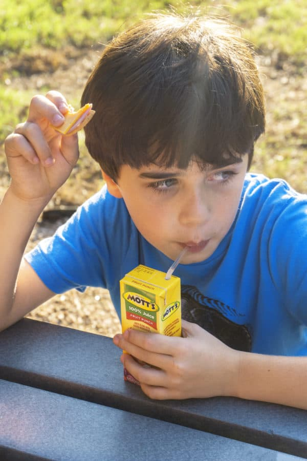 child with blue shirt drinking from a juice box inside and holding a cracker with ham and cheese from a lunchmakers pack