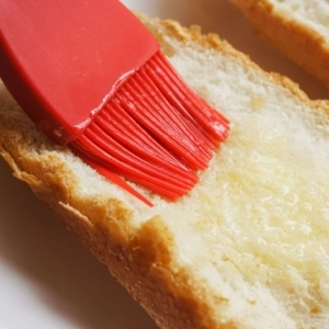 brushing melted butter on bread