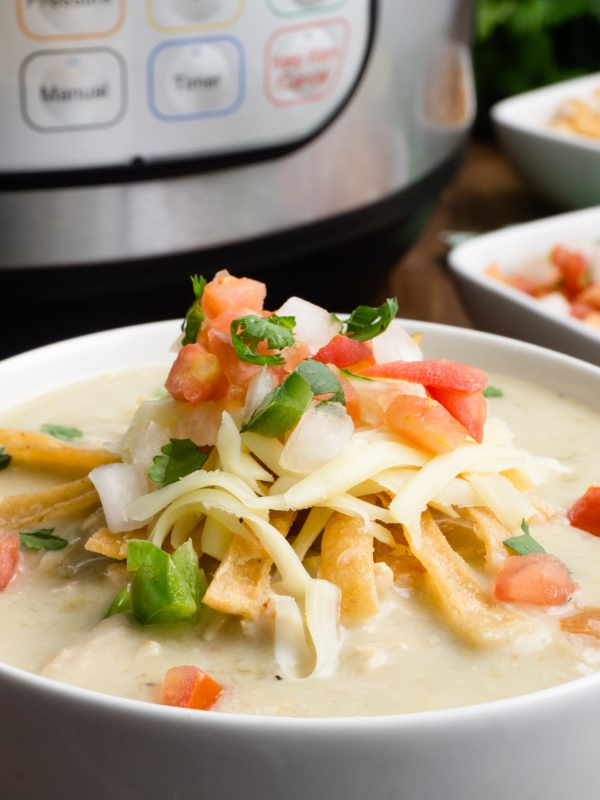 a bowl fo instant pot chicken enchilada soup topped with fried tortilla strips, shredded cheese, and pico de gallo