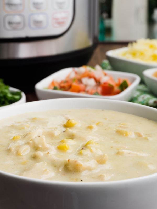 a close up of a bowl of creamy instant pot enchilada soup with corn with the toppings and the instant pot in the background