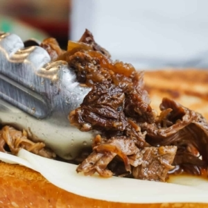 placing cooked chuck roast on a french bread topped with provolone to make french dip sandwiches