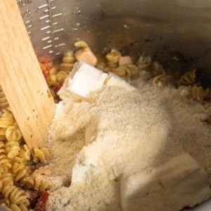 adding cream cheese and parmesan to tuscan chicken pasta in the instant pot