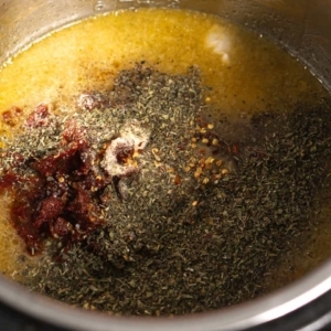 adding spices to the instant pot for tuscan chicken pasta