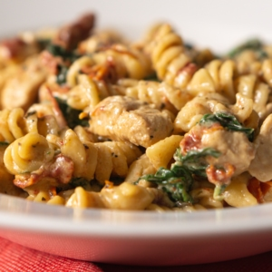 a close up of tuscan chicken pasta served on a plate
