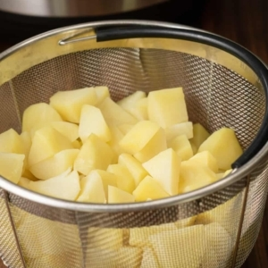 a wire mesh basket filled with cooked potatoes sitting on the counter