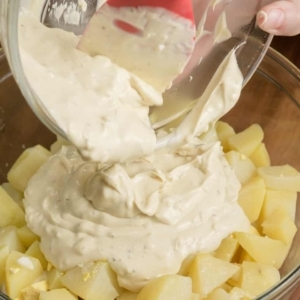 adding a creamy sauce to chopped potatoes in a mixing bowl
