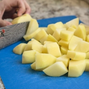 chopping potatoes with a knife on a cutting board full of chopped potatoes