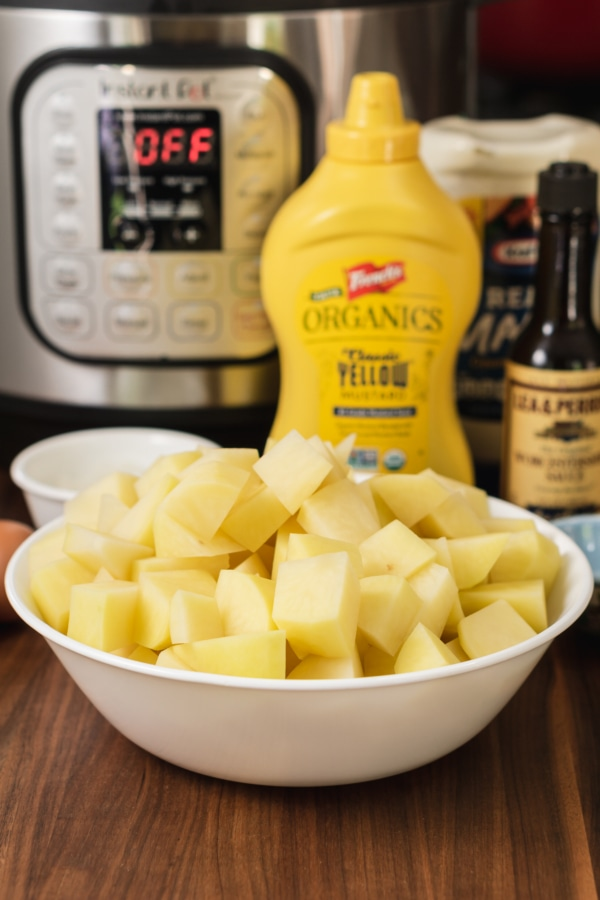 the ingredients for making potato salad sitting on the counter in front of the instant pot including a bowl of chopped potatoes, a bottle of yellow mustard, a bottle of mayonnaise, and a bottle of Worcestershire sauce