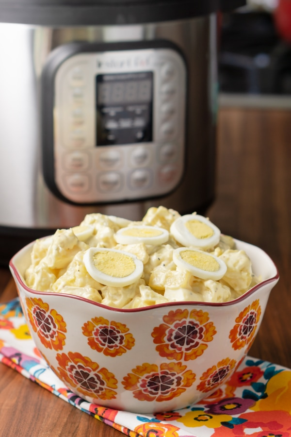 a serving bowl filled with potato salad and topped with slices of egg sitting in front of the instant pot