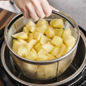 lowering a mesh basket filled with chopped potatoes into the instant pot
