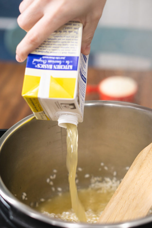 pouring chicken stock into the Instant Pot to make risotto